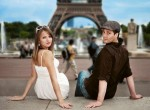 Young couple sitting in front of the Eiffel Tower, direct view, Paris, France, Europe