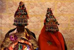 A bride and groom wearing traditional handmade garlands wait for their wedding to start during a mass marriage ceremony in Karachi