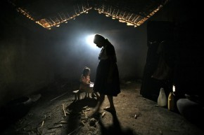 Girl does her homework as her mother makes corn tortillas for lunch in their adobe home on the outskirts of Chiquimula