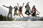 Portrait of exuberant friends jumping in snowy field