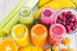 Multicolored smoothies in bottles of mango, orange, banana, celery, berries, on a wooden table.
